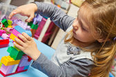 Little girl is playing with building bricks — Stock Photo