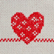 Red heart embroidered in cross stitch on canvas — Stock Photo