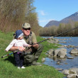 Stock Photo: Father and daughter fishing on river
