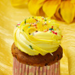 Delicious vanilla cup cake with yellow icing — Stock Photo