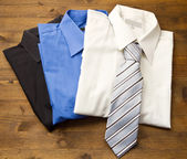 Close up of stacked shirts with tie. — Stock Photo