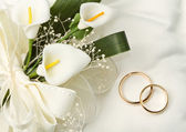 Wedding rings with calla bouquet — Stock Photo