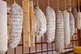 Row of hanging salamis — Stock Photo