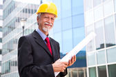 Happy, smiling older architect looking out — Stock Photo