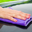 A Hand drying a back car with a synthetic  cloth — Stock Photo