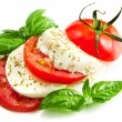 Tomato and mozzarella with basil leaves — Stock Photo