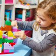 Little girl is playing with building bricks — Stock Photo #28169983