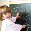 Child draws with chalk on the blackboard — Stock Photo #29090461