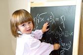 Kind zeichnet mit kreide an die tafel — Stockfoto