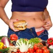Fat woman with hamburger and vegetables — Stock Photo