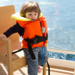 Little girl dressed in life jacket stands in cabin's balcony — Stock Photo