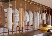 Row of hanging salami — Stock Photo