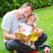 Father reading a book to his daughter while laying on the grass — Foto de Stock