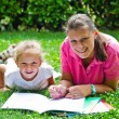 Happy mother drawing a book with baby girl in garden — Stock Photo