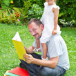 Stock Photo: Father reading book to his daughter while laying on grass