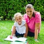 幸せな母の庭で女の赤ちゃんを持つ本を描画 — ストック写真