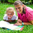 Happy mother drawing a book with baby girl in garden — Stock Photo #30091631
