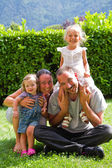 Portrait of happy family on the green lawn — Stock Photo