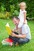 Father reading a book to his daughter while laying on the grass — Stock Photo