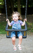 Happy little girls on a swing — Stock Photo