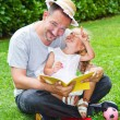 Stock Photo: Father reading book to his daughter while laying on grass in garden