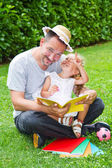 Father reading a book to his daughter while laying on the grass in the garden — Stock Photo