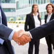 Handshake in front of business people — Stock Photo
