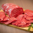Huge red meat chunk and steak on wood table — Stock Photo #31067177