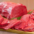 Huge red meat chunk and steak on wood table — Stock Photo