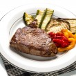 Delicious beef steaks on white dish with grilled vegetables — Stock Photo