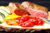 Delicious beef steaks on wooden table — Stock Photo