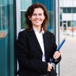 Young confident businesswoman with folder  near the office build — Stock Photo