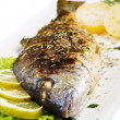 Stock Photo: Grilled gilt head sebream on plate with lemon and rosemary and