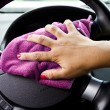 Woman's hand with microfiber cloth polishing wheel of a car — 图库照片