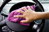 Woman's hand with microfiber cloth polishing wheel of a car — Stockfoto