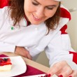 Beautiful young chef decorating delicious dessert — Stock Photo #31577599