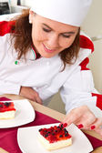 Beautiful young chef decorating delicious dessert — Stock Photo