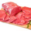 Huge red meat chunk and steak on wood table — Stock Photo #32482049
