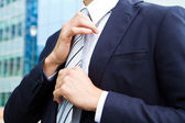 Business man adjusting tie — Stock Photo