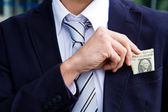 Businessman outside office taking banknotes — Stock Photo