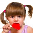 Little girl eating red heart lollipop — Stock Photo