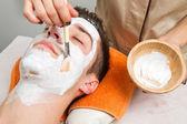 Θεραπευτής εφαρμόζει μια μάσκα προσώπου για ένα όμορφο νεαρό άνδρα σε ένα spa治疗师将口罩应用到一个美丽的年轻人,在一个水疗中心 — 图库照片