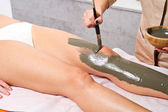Relaxing woman lying on a massage table receiving a mud treatmen — Foto Stock