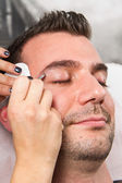 Beautician plucking a beautiful man eyebrows with tweezers in a — Stock Photo