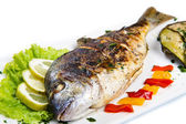 Grilled gilt head sea bream on plate with lemon ,salad and grill — Stock Photo