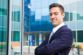 Smiling young businessman standing outside a building — Stock Photo