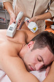 Young man receiving laser epilation on beauty center — Stock Photo