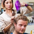 Beautiful man at the hairdresser blow drying his hair — Stock Photo