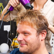 Beautiful man at the hairdresser blow drying his hair — Stock Photo #36516567