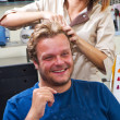 Beautiful man at the hairdresser blow drying his hair — Stock Photo #36516581